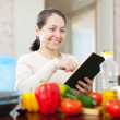 Woman cooking with cookbook in the kitchen — Stockfoto