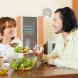 Middle-aged woman and man having vegetarian dinner at home — Stock Photo