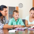 Family of three doing homework in home — Stock Photo #38696299