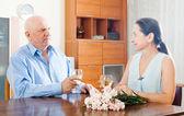 Elderly man with mature woman having wine — 图库照片