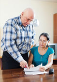 Mature couple fills in questionnaire together — Stock Photo
