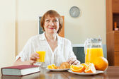 Mature woman having breakfast with book — Stock Photo