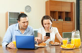 Couple using laptop during breakfast at home — Stock Photo