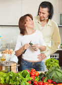 A man and a woman with vegetables in the kitchen — Stock Photo
