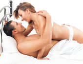 Smiling adult couple having sex on bed in bedroom interior — Stock Photo