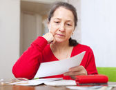 Serious woman reads payment bills — Stock Photo