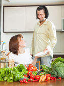 An attractive man and beautiful woman with vegetables in the kit — Stock Photo