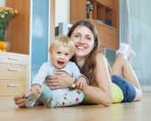 Happy long-haired mom and child on wooden floor — Stock Photo