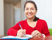 Smiling mature woman fills in documents — Stock Photo