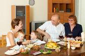 Happy family around festive table — Stock Photo