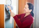 Reife frau reinigung möbel — Stockfoto