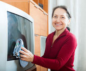 Mature woman dusting TV — Stock Photo