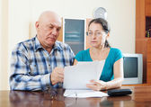 Mature man with wife reading documents — Stock Photo