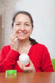 Mujer madura pone crema en la cara — Foto de Stock