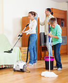 Family with teenage boy cleaning in living room — Stock Photo