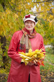 Smiling woman in autumn with maple posy — Stock Photo