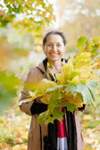 Happy mature woman with maple posy — Stock Photo