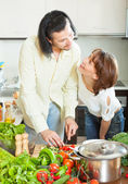 A woman and a man with vegetables in the kitchen — Stock Photo