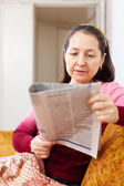 Pensive woman reading newspaper — Stock Photo