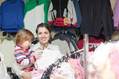 Cheerful mother with baby at clothes store — Stock Photo