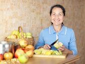 Woman cuts apples — Stock Photo