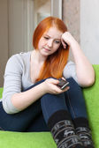 Red-haired teenager girl waits telephone call — Stock Photo