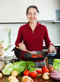 Positive mature woman cooking with frying pan — Stock Photo