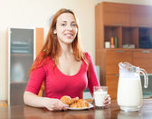 Smiling brunette woman having breakfast with juice in morning at — Stock Photo