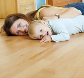 Happy mom and child on wooden floor — Stock Photo