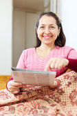 Mature woman pointing to newspaper — Stock Photo