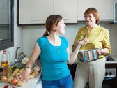 Mature woman and adult daughter cooking food — Stock Photo