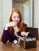 Teen girl looks jewelry in treasure chest — Stock Photo