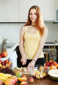 Happy young woman cutting fruits for salad — Stock Photo