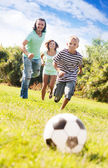 Adult couple and teenager playing with soccer ball — Stock Photo