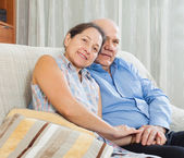 Mature couple sitting on couch — Stock Photo