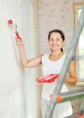 Woman paints wall with roller — Stock Photo