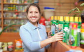 Woman chooses agricultural chemistry at store — Stock Photo