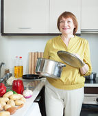 Mature housewife with pan in home kitchen — Stock Photo