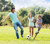 Middle-aged couple and teenager playing with soccer ball — Foto Stock