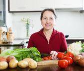 Mature woman cutting tomato — Stock Photo