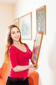 Long-haired girl in red hanging the pictures — Stock Photo