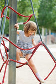 Girl in dress climbing on ropes — Stock Photo