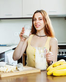 Girl in yellow drinking milk shake with bananas — Stock Photo
