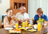 Portrait of cheerful three generations family eating friuts wit — Stock Photo