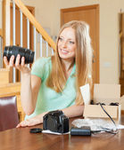 Young girl unpacking new digital camera in home interior — Stok fotoğraf