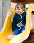 Happy child on slide at playground — Stock Photo