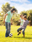 Happy parents with teenage son playing with ball — Stock Photo