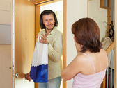 Man gives a gift to women at home — Stock Photo