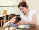 Mom teaches malekuyu girl sculpt dough figurines — Stock Photo