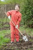 Woman working with shovel in orchard — Stock Photo